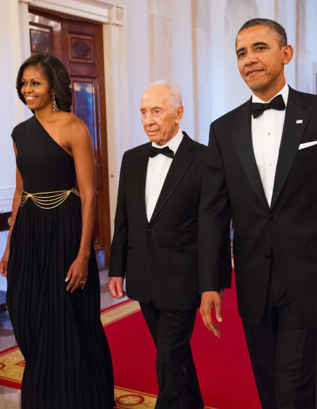 US President Barack Obama (R) and First Lady Michelle Obama enter the East Room with Israeli President Shimon Peres for a dinner where he would be presented with the Presidential Medal of Freedom June 13, 2012at the White House in Washington, DC. The medal is the highest civilian honour in the US. AFP PHOTO/Mandel NGAN (Photo credit should read MANDEL NGAN/AFP/GettyImages)